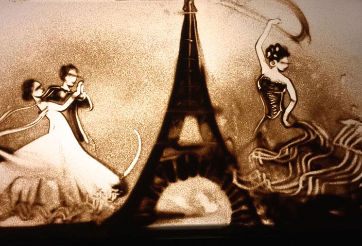 Sandbild von Tänzern neben dem Eiffelturm