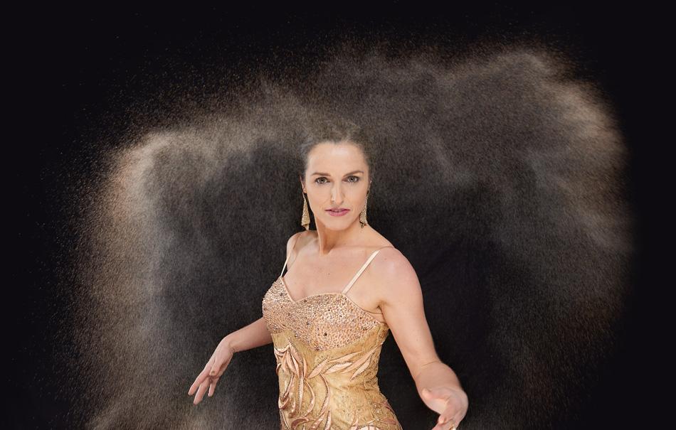 Frauke Menger schmeißt am Sandtisch Sand in die Luft