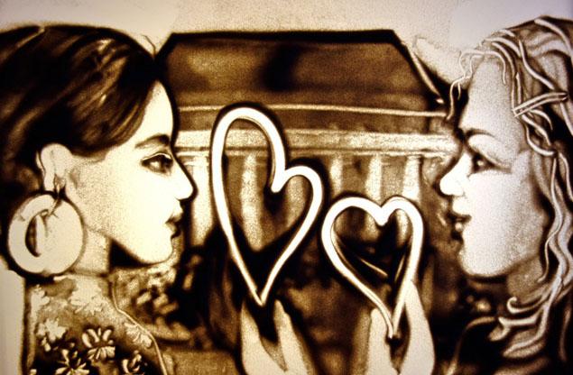 Sandbild zweier Menschen mit Herzen dazwischen