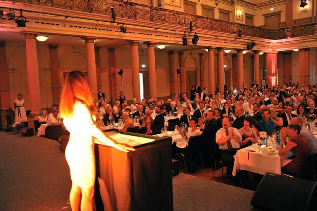 Frauke Menger am Sandtisch vor Publikum beim Auftritt für die Deutsche Bank