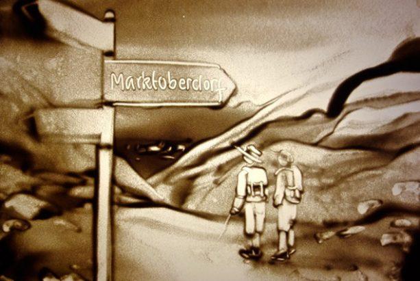 Sandbild von 2 Wanderern vor einem Wegweiser