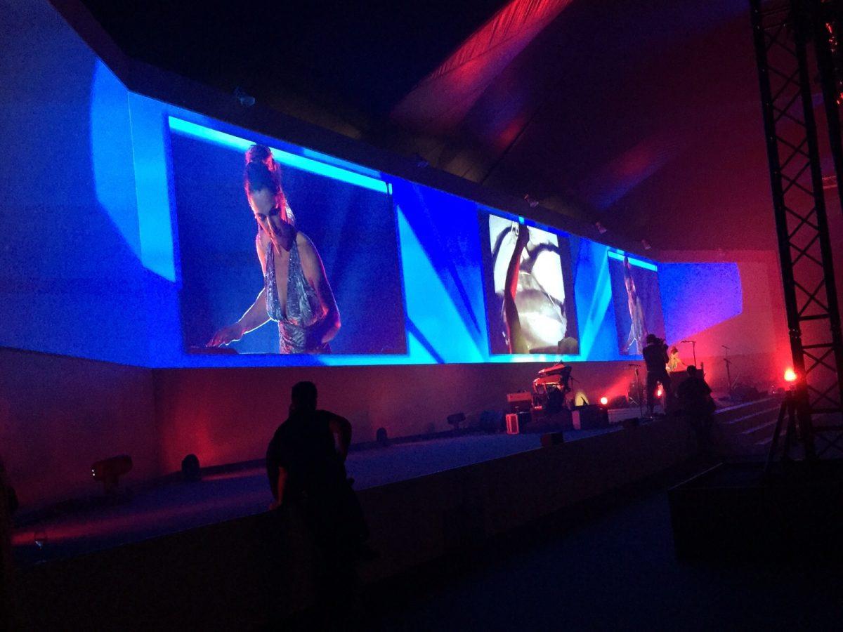 Frauke Menger auf einer großen Bühne mit 3 Leinwänden